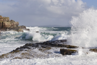Waves crashing over rocky coastline